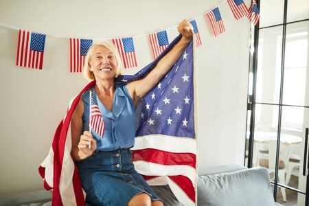 Portrait of happy mature woman waving American flag and smiling happily at camera, copy space