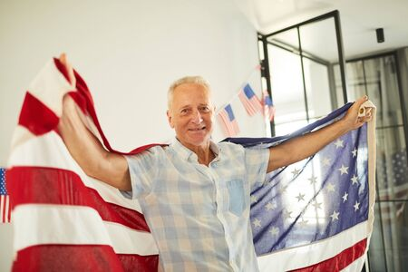 Portrait of happy senior man waving American flag and smiling happily at camera, copy space 写真素材