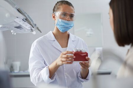 Portrait of young female dentist wearing protective mask and holding tooth model while consulting patient in clinic, copy space