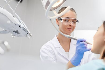 Low angle portrait of smiling female dentist working with patient in clinic, copy space