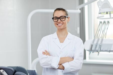 Waist up portrait of young female doctor wearing glasses smiling at camera while posing in office, copy space Stock Photo