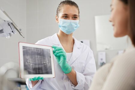 Portrait of young female dentist showing teeth x-ray image to patient during consultation in clinic, copy space
