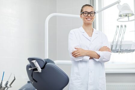 Portrait of young female doctor wearing glasses smiling at camera while posing with dental chair, copy space