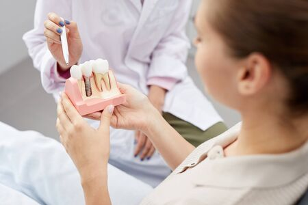 Closeup of unrecognizable female doctor pointing at tooth model while consulting patient, copy space Stock Photo