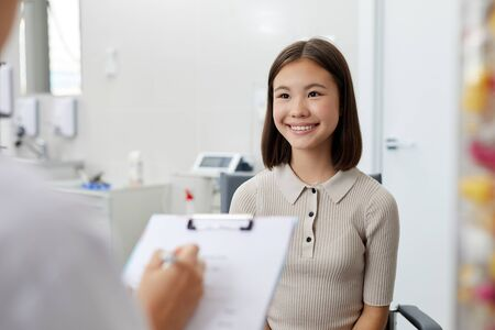 Waist up portrait of little Asian girl looking at doctor and smiling happily during consultation in clinic, copy space