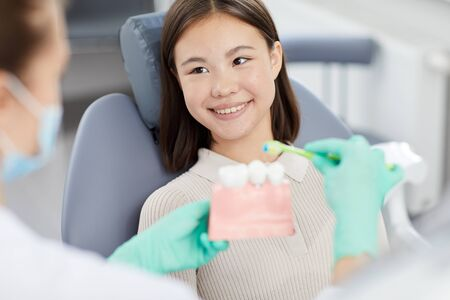 Portrait of smiling Asian girl sitting in dental chair and listening to dentist holding tooth model, copy space Stock Photo