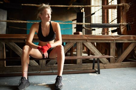 Full length portrait of female boxer waiting by boxing ring at sports club and looking away, copy space