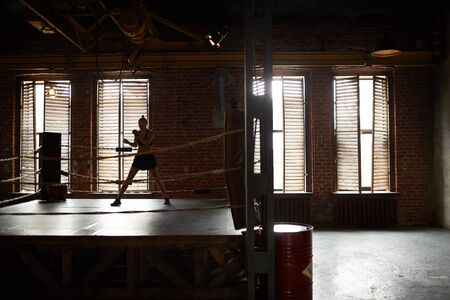 Dramatic wide angle view at boxing club with female boxer practicing in ring, copy space Foto de archivo