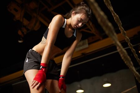 Ritratto ad angolo basso di una sportiva esausta che si ferma per riprendere fiato durante l'allenamento, copia spazio Archivio Fotografico