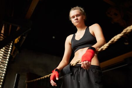 Dramatic low angle portrait of tough female boxer looking down at camera while standing in boxing ring, copy space