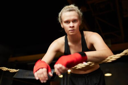 Dramatic portrait of tough female boxer looking at camera while standing in boxing ring, copy space