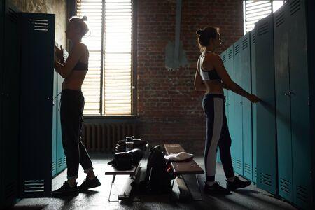 Vista lateral de dos mujeres duras en vestuario cutre en club deportivo, espacio de copia
