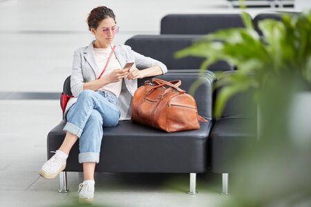 Chica joven pensativa con gafas de sol rosas sentado en un sofá de cuero en el aeropuerto y usando un gadget mientras espera la salida