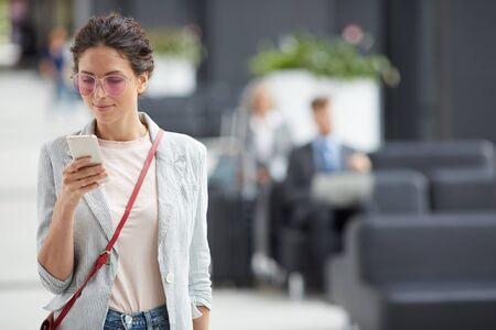 Content attractive stylish girl in sunglasses wearing stripped jacket and red bag checking phone on move