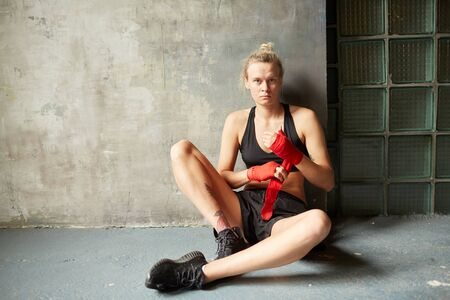 Dramatic full length portrait of female boxer looking at camera while sitting by concrete wall in sports club, copy space