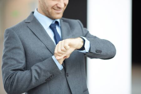 Close-up of smiling businessman in gray suit standing in lobby and checking time on wristwatch Stock Photo