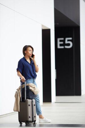 Giovane donna pensierosa in abito casual in piedi con una valigia con ruote in aeroporto e che comunica al telefono