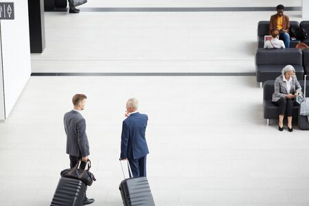 Directly above view of businessmen in suits holding handles of wheeled suitcases and discussing business trip in airport