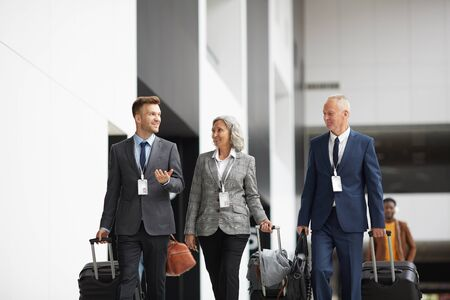 Group of confident company managers in suits walking with luggage in airport and discussing business trip Фото со стока