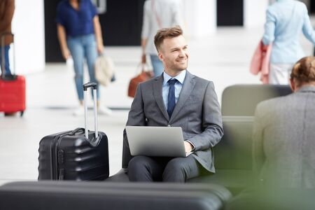 Positive inspired young entrepreneur in formalwear sitting in airport area using laptop while working on presentation