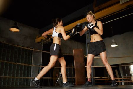 Full length portrait of two women fighting in boxing ring, copy space Stockfoto