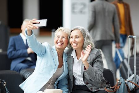 Cheerful mature multi-ethnic ladies sitting on sofa in airport and photographing together on smartphone