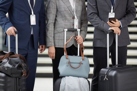 Close-up of unrecognizable people in suits wearing badges on ribbons standing in line and holding luggage