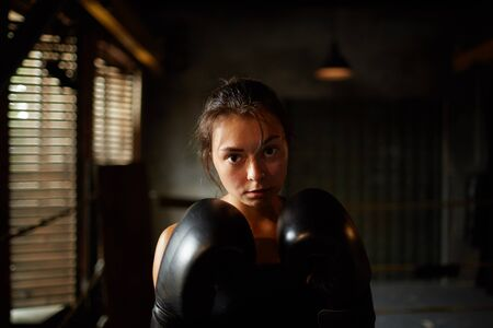 Dramatic portrait of young woman looking at camera with determination during boxing practice in dark room, copy space