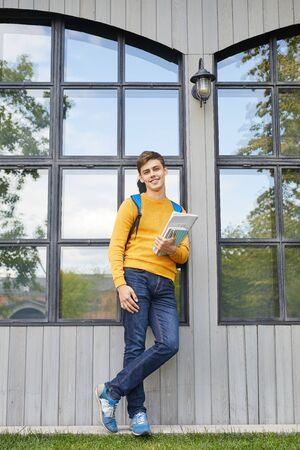 Full length portrait of smiling student posing confidently outdoor in college campus, copy space