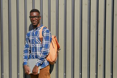 Waist up portrait of African student looking at camera while posing by ribbed wall outdoors in college campus, copy space