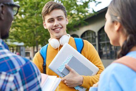 Ritratto in vita di uno studente universitario allegro che parla con gli amici all'aperto nel campus, copia spazio