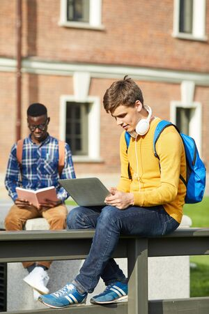 Full length portrait of contemporary college student using laptop sitting on table outdoors in campus, copy space