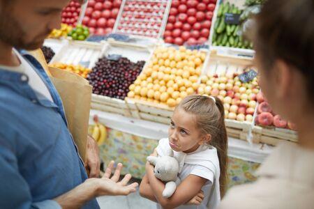 Vista de ángulo alto en niña mimada que se niega a cooperar con los padres en el mercado de agricultores, espacio de copia
