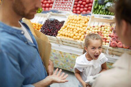 Vista de ángulo alto en niña mimada gritando a los padres en el supermercado, espacio de copia