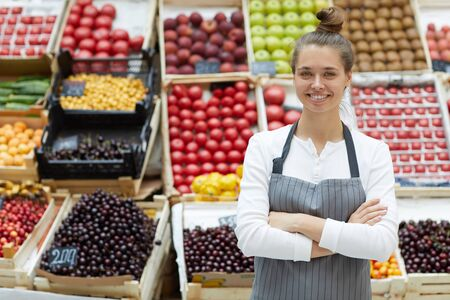 Waist up portrait of pretty young saleswoman posing with fresh fruits and vegetables at farmers market, copy space Imagens