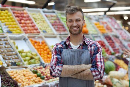 Ritratto in vita di un bel giovane che lavora al supermercato e sorride alla macchina fotografica mentre posa vicino al banco della frutta, copia spazio
