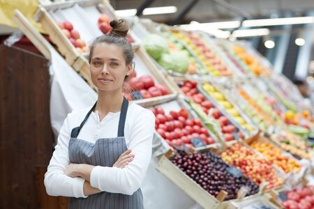 Waist up portrait of pretty young saleswoman looking at camera while posing by fresh fruits and vegetables at supermarket, copy space