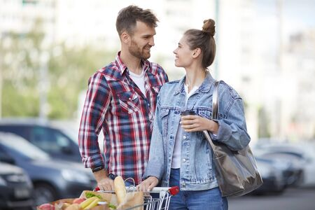 Waist up portrait of contemporary young couple pushing shopping cart with groceries in parking lot, copy space