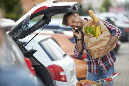Portrait of smiling young man speaking by phone while packing groceries into car trunk , copy space