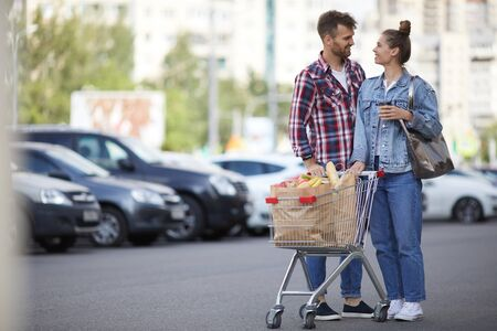 Full length portrait of contemporary young couple pushing shopping cart with groceries in parking lot, copy space Stock Photo
