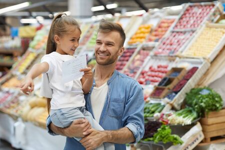 Waist up portrait of smiling father shopping with little girl at farmers market, copy space Imagens