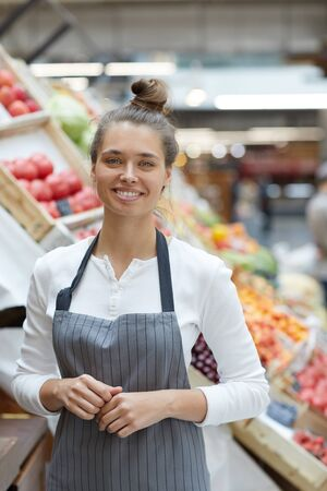 Waist up portrait of pretty young saleswoman smiling at camera while posing by fresh fruits and vegetables at supermarket, copy space Imagens