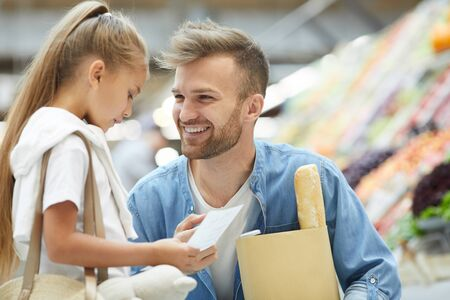 Portrait of handsome young man smiling at little girl while shopping at farmers market, copy space
