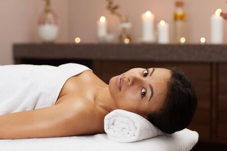 Portrait of beautiful mixed-race woman looking at camera while relaxing in luxury SPA, copy space