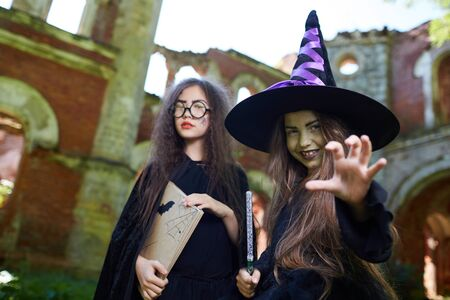 Waist up portrait of two teenage witches looking at camera while posing in spooky castle on Halloween, copy space