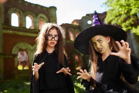 Waist up portrait of two spooky little witches posing outdoors on Halloween, copy space