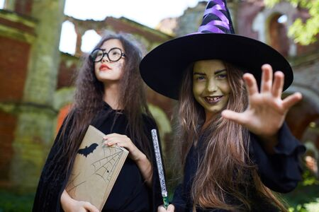 Waist up portrait of two teenage witches looking at camera while posing in spooky castle on Halloween
