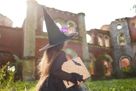 Back view portrait of little witch walking by abandoned castle on Halloween, copy space Banco de Imagens