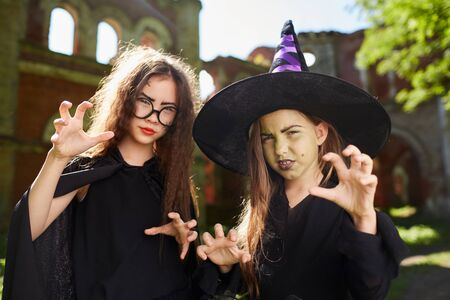 Waist up portrait of two spooky little witches posing outdoors on Halloween