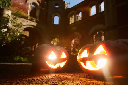 Halloween background of two lit Jack o lanterns in front of castle, copy space
